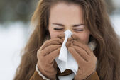 Young woman blowing nose in winter outdoors — Stock Photo