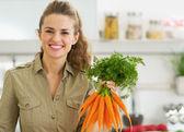Heureux jeune maîtresse de maison maintenant des tas de carottes en cuisine — Photo