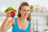 Smiling young woman holding bunch of radishes — Stock Photo
