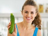Smiling young woman showing fresh zucchini — Stock Photo