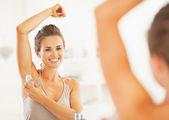 Woman applying roller deodorant — Stock Photo