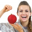 Happy young womin sweater showing christmas ball — Stock Photo #33780413