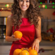 Happy young housewife decorating christmas plate with oranges — Stock Photo