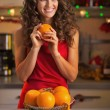 Happy young housewife with oranges in christmas decorated kitche — Stock Photo