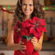 Happy young woman in red dress holding christmas rose — Foto de Stock