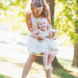 Happy mother and baby having fun in park — ストック写真