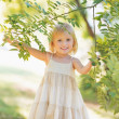 Portrait of smiling baby girl looking out from tree foliage — Stock Photo