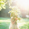 Baby girl looking out through tree foliage — Stock Photo