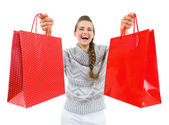 Happy young woman in sweater showing christmas shopping bags — Stock Photo