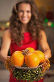 Closeup on christmas decorated plate with oranges in hand of you — Stock Photo