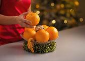 Gros plan sur la jeune femme au foyer, décoration assiette de Noël avec orang — Photo