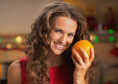 Portrait of smiling young housewife with orange in christmas dec — Stock Photo