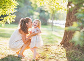 Portrait of happy mother and baby playing outdoors — Stock Photo