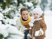 Portrait of happy mother and baby in winter park — Stock Photo