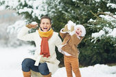 Happy mother and baby throwing snowballs in winter park — Stock Photo