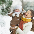 Happy mother and baby playing with snow on branch — Stock Photo