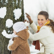 Happy mother and baby making face for tree using snow — Stock Photo