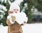 Baby holding big snowball — Stock Photo