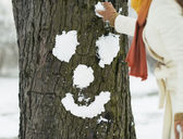 Young woman making face for tree using snow — Stock Photo
