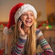 Smiling teenage girl in santa hat talking mobile phone in christmas decorated kitchen — Stock Photo