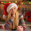 Portrait of thoughtful teenage girl in santa hat with hammer and piggy bank — Stock Photo #36989155
