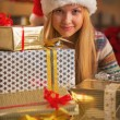 Happy teenage girl in santa hat with stack of christmas present boxes — Stock Photo
