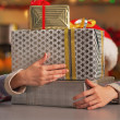 Happy teenage girl hiding behind stack of christmas present boxe — Stock Photo
