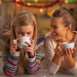 Smiling two girlfriends having christmas snacks in christmas decorated kitchen — Stock Photo