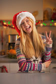 Happy teenage girl in santa hat showing victory gesture in christmas decorated kitchen — Stock Photo