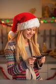 Smiling teenage girl in santa hat writing sms in christmas decorated kitchen — Photo