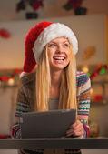 Happy teenage girl in santa hat using tablet pc — Stock Photo