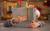 Happy teenage girl hiding behind stack of christmas present boxe — Stock Photo