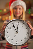 Closeup on smiling teenage girl in santa hat showing clock — Stock Photo