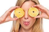 Portrait of happy teenage girl holding lemon in front of eyes — Stockfoto