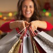 Closeup on christmas shopping bags in hand of smiling young woman — Stock Photo #36991557