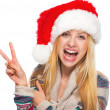Portrait of smiling teenage girl in santa hat showing victory gesture — Stock Photo