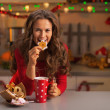 Happy young woman having eating christmas cookies in kitchen — Stock Photo