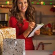 Happy young woman with shopping bags checking list of gifts — Stock Photo #36991623