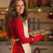 Happy young housewife with pan of christmas cookies — Stock Photo #36991795