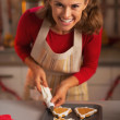 Smiling young housewife decorating christmas cookies in kitchen — Stock Photo #36992117