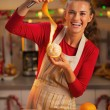 Happy young housewife showing orange peel in christmas decorated — Stock Photo