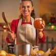 Housewife showing orange jam in christmas decorated kitchen — Stock Photo #36992265