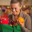 Smiling young housewife sorting purchasing after christmas shopp — Stock Photo #36992351