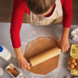 Young housewife rolling pin dough in kitchen — Stok fotoğraf
