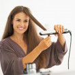 Happy young woman straightening hair with straightener — Stock Photo