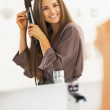 Smiling woman curling hair with straightener — Stock Photo