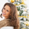 Young woman sitting in front of christmas tree — Stock Photo