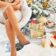 Closeup on young woman sitting near christmas tree — Stock Photo