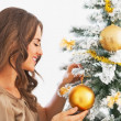 Happy young woman decorating christmas tree with christmas ball — Stock Photo