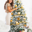 Portrait of happy young woman decorating christmas tree — Stock Photo